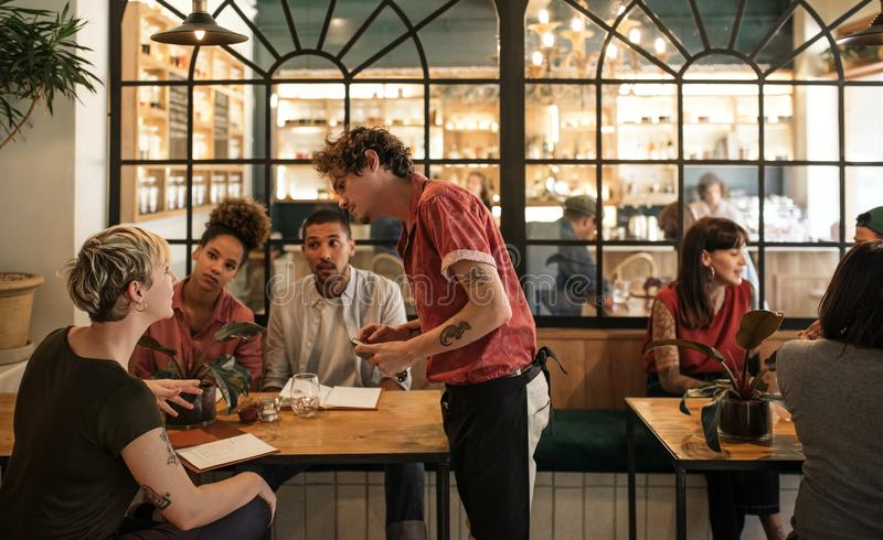 Waiter taking orders from customers sitting in a bistro royalty free stock photo