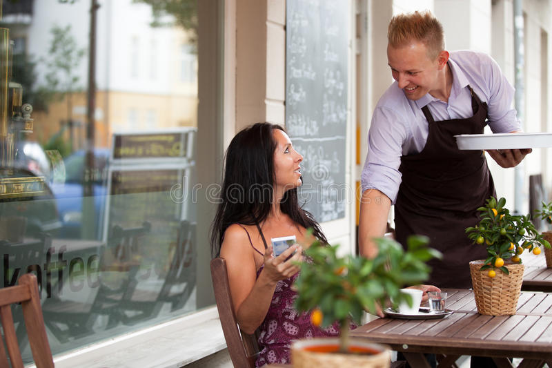 Waiter with a tray in a coffee shop stock image