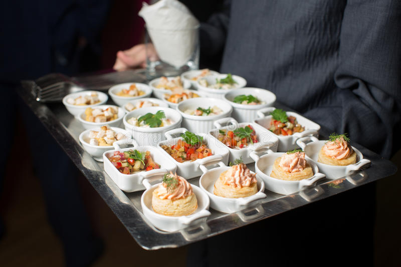 A waiter with a tray of snacks at a banquet stock photos