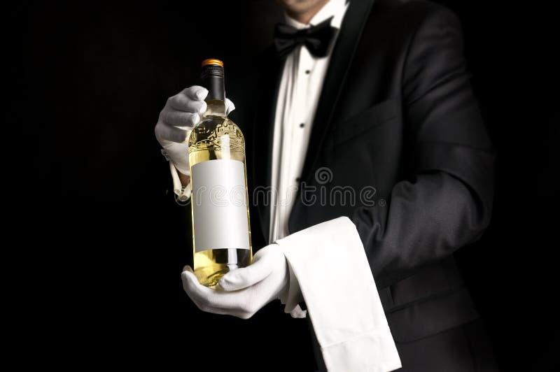 Waiter in tuxedo holding a bottel of white wine stock photos