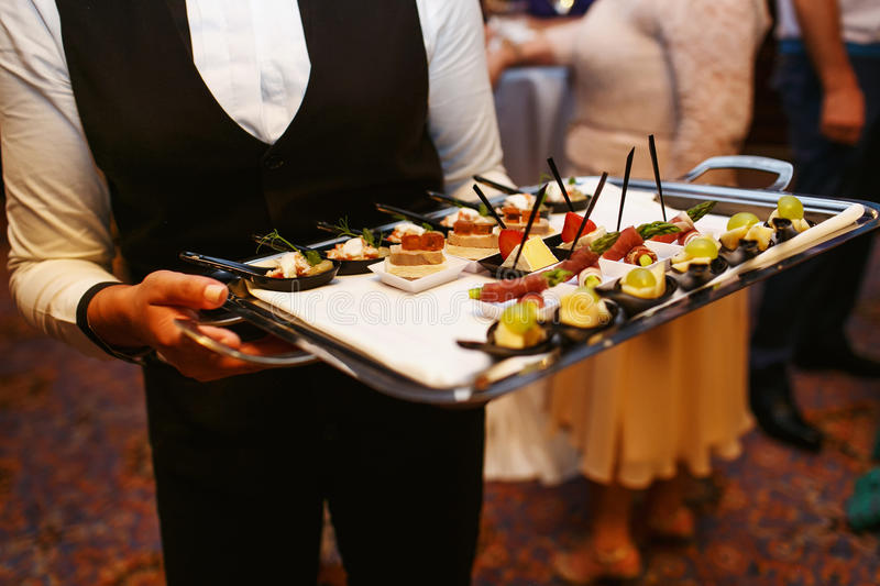 Waiter work. Set a variety of meat, fish and fruit snacks at the restaurant to celebrate the solemn event stock image