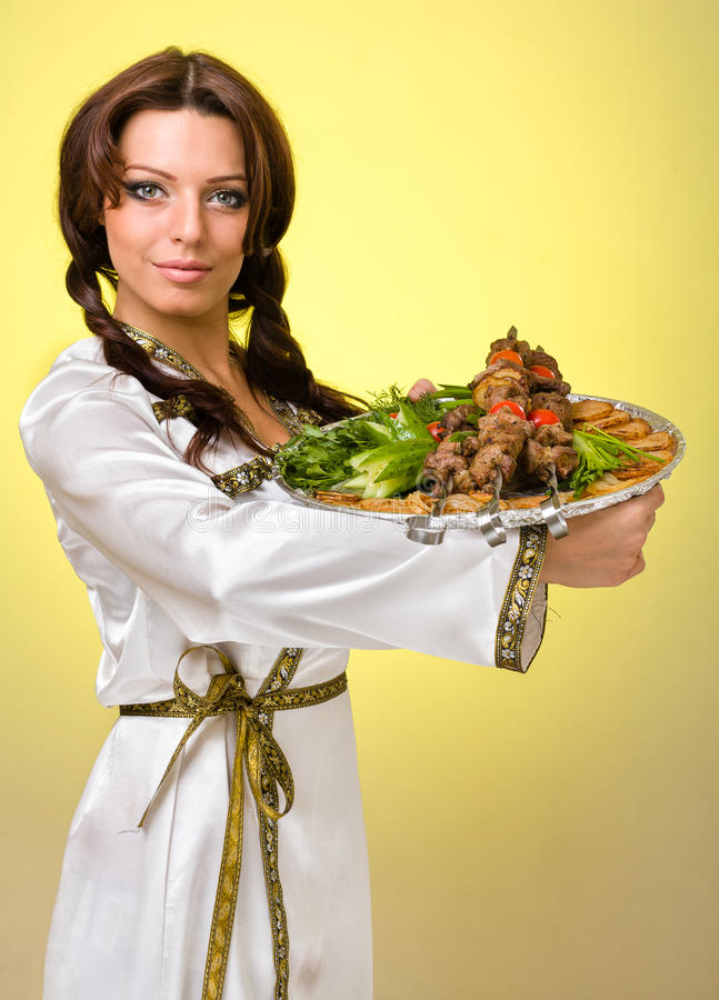 Waiters carrying plates with meat on yellow background royalty free stock images