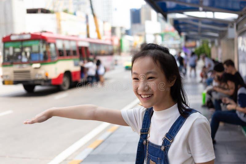 Waithing buss för asiatisk gullig flicka på hållplatsen på gatan av staden, lifes arkivbilder