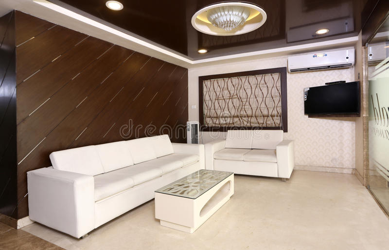 WAITING AREA. Of a Restaurant has a good background wall wooden finish with white sofa and a centre table stock photos