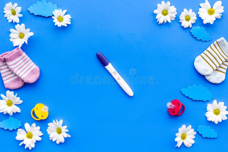 Waiting for a baby with positive pregnancy test and flowers blue background top view mockup royalty free stock photo