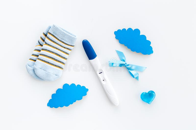 Waiting for a baby with positive pregnancy test, socks and hearts white background top view stock image