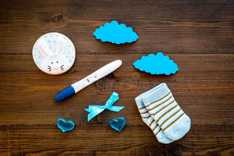 Waiting for a baby with positive pregnancy test, socks and hearts wooden background top view royalty free stock photo