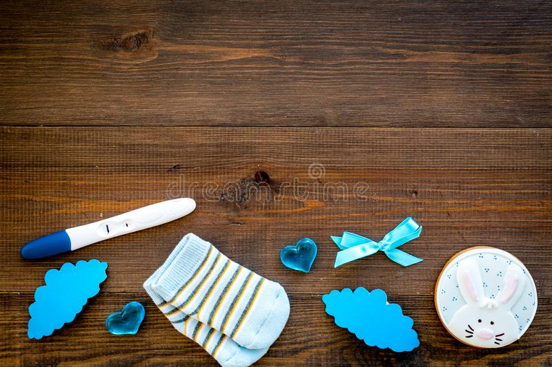 Waiting for a baby with positive pregnancy test, socks and hearts wooden background top view mockup royalty free stock photos