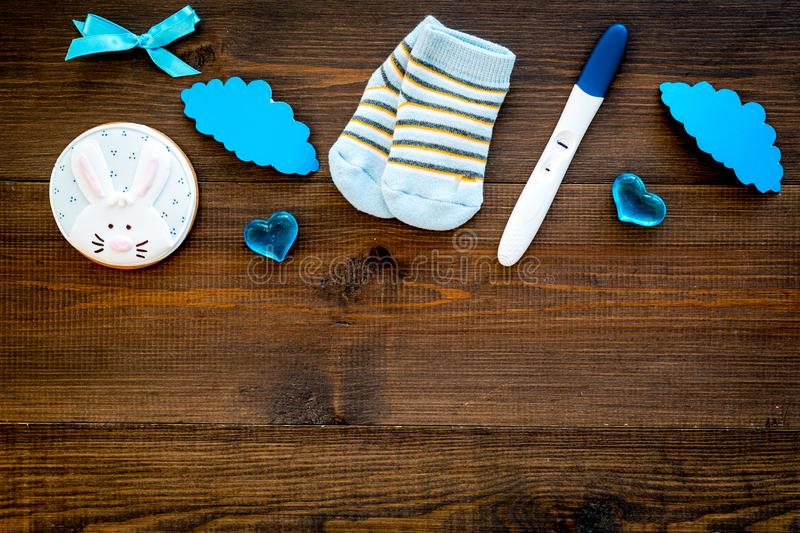 Waiting for a baby with positive pregnancy test, socks and hearts wooden background top view mockup stock images