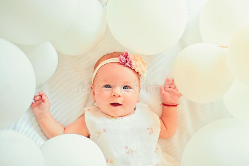 Waiting for a baby. Small girl. Happy birthday. Portrait of happy little child in white balloons. Sweet little baby. New royalty free stock photography