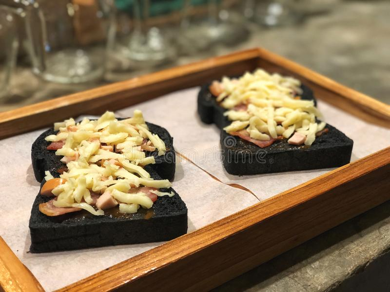 Waiting bake, Mini pizza made by charcoal bread topped with bacon and cheese. In wooden tray with cafe light royalty free stock photography