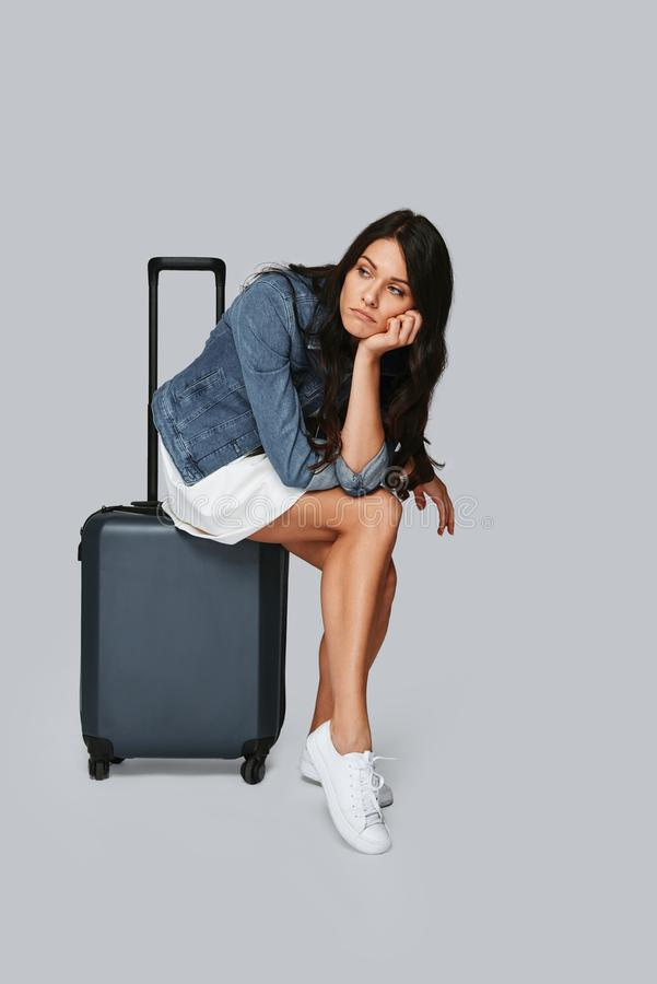 Waiting for check-in. Bored young woman looking away while sitting on the suitcase against grey background stock photography