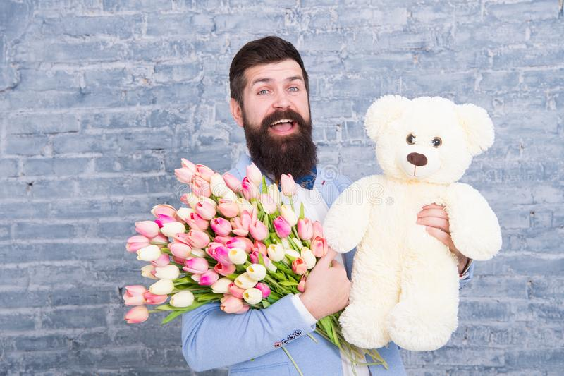 Waiting for darling. Man well groomed wear tuxedo bow tie hold flowers tulips bouquet and big teddy bear toy. Invite her. Dating. Romantic gift. Romantic man stock image