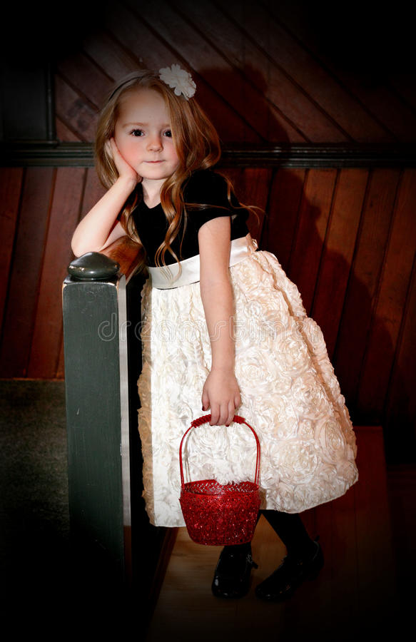 Waiting Flowergirl. A little bright eyed 5 year old flower girl with a bow in her long hair holding a red basket wearing a pretty dress stands waiting. Shallow stock photos