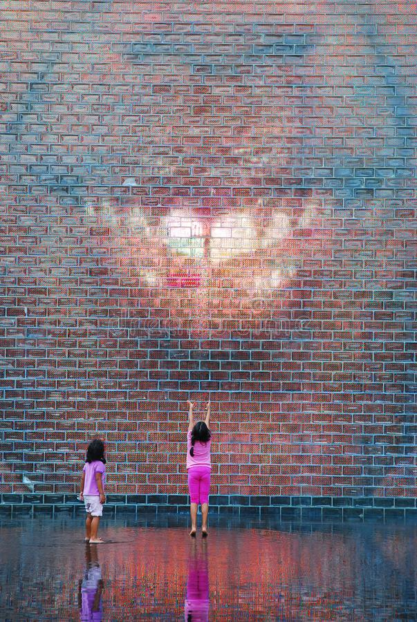 Waiting for the Fountain. Two young girls wait for the Crown Fountain to gush water in Millenium Park, Chicago royalty free stock photo