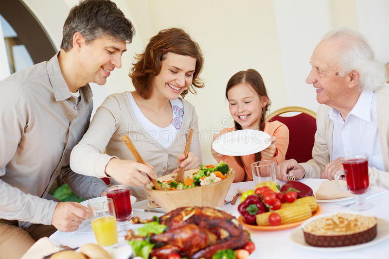 Waiting for garnish. Portrait of affectionate family by Thanksgiving table stock images