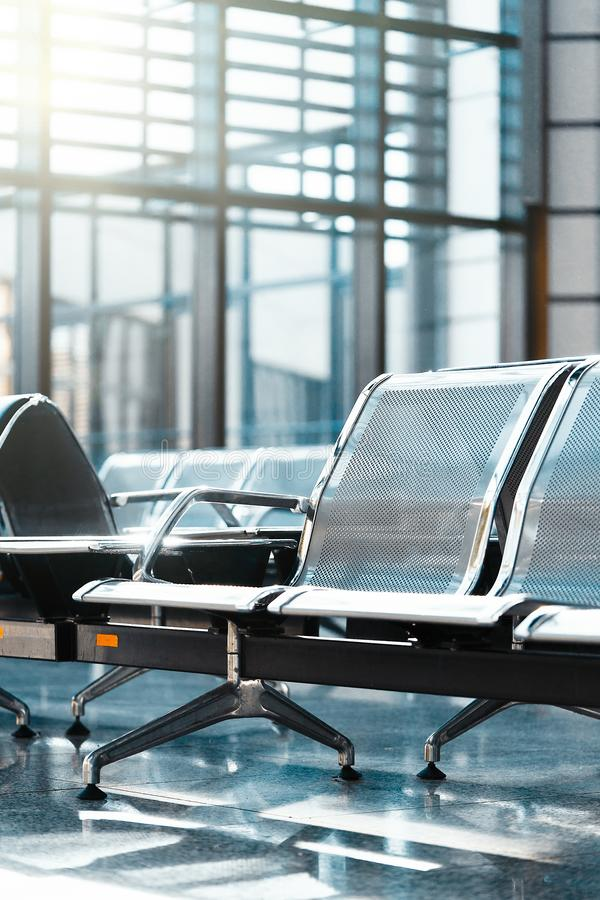 Waiting hall in modern airport terminal, focus on chairs. Vacation concept. royalty free stock image