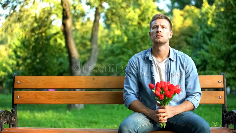 Waiting handsome man with red flowers sitting park bench, outdoor date affection stock photography