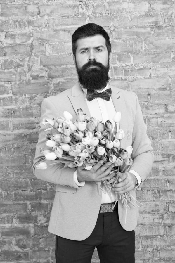 Waiting for his girlfriend. Romantic man with flowers. Romantic gift. Macho getting ready romantic date. Tulips for royalty free stock images