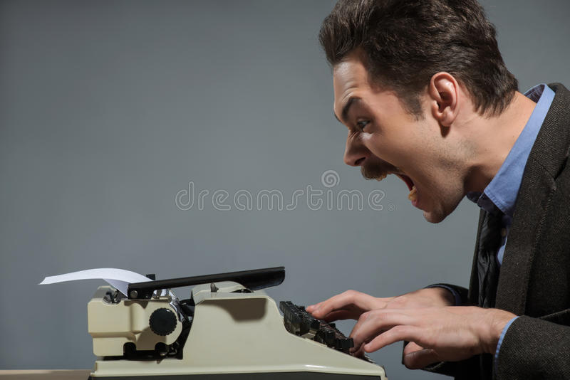 Waiting for idea. Young author screaming. Waiting for idea. Young nerd author typing something at the typewriter and screaming while sitting at his working place stock photos