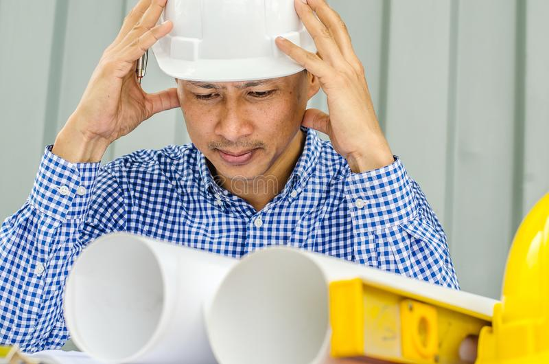Waiting for inspiration. Asia Engineer serious thinking, young man and looking away while sitting at container royalty free stock images