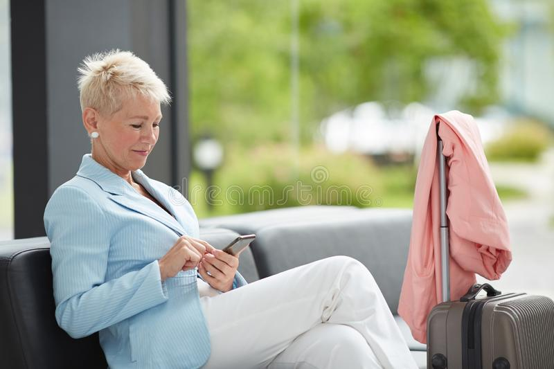 Waiting for journey. Content beautiful mature lady with short blond hair sitting in airport with wheeled suitcase and coat and using smartphone while waiting for stock photography