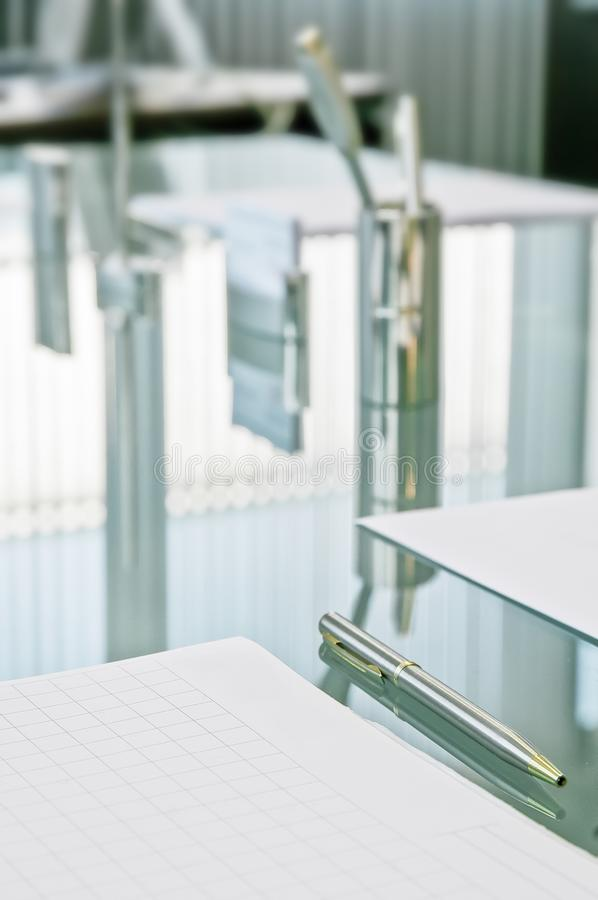 Waiting for the meeting. The crystal table set with paper pads for notes, pens and business cards reflects the curtains with. Vertical strips stock photo