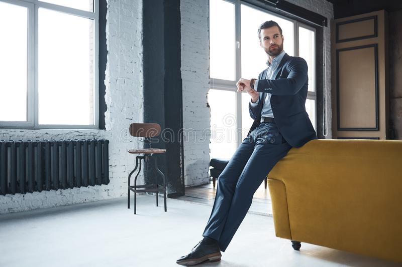 Waiting for a meeting. Serious handsome businessman weared in fashionable suit is looking at watch and waiting royalty free stock image