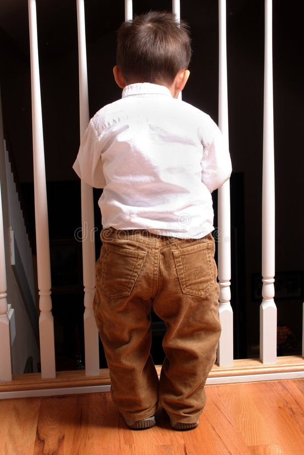 Waiting For Mom. A baby boy, looking through the railing for his mom royalty free stock photo