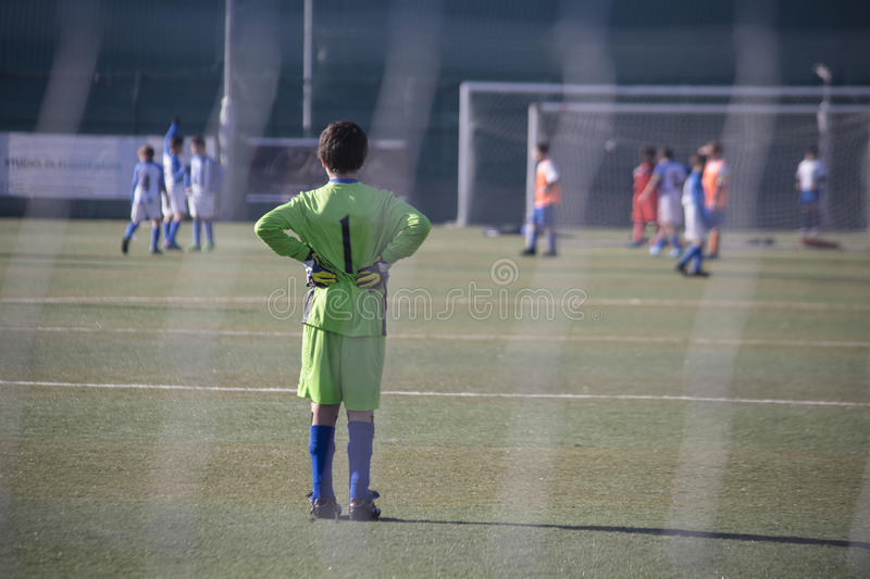 Waiting for opponents. A young Goalkeeper waiting for opponents during a football match royalty free stock photo
