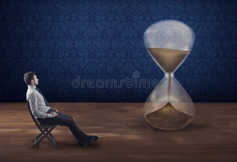Waiting in patience. The concept of waiting patient. Businessman sitting on a chair and watching time passing by into a hourglass. The concept of waiting royalty free stock image