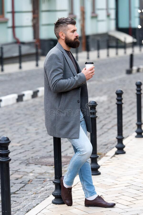 Waiting for someone in street. Man bearded hipster drink coffee paper cup. Businessman well groomed enjoy coffee break stock photography