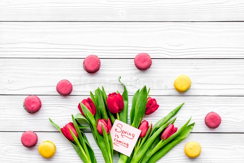 Waiting for spring. Spring is coming lettering near bouqet of red tulips and sweets macarons on white wooden background. Top view royalty free stock images