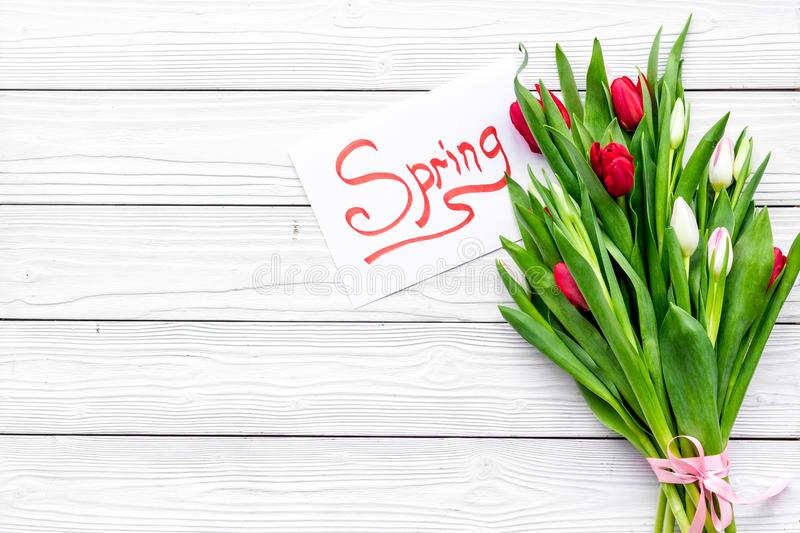 Waiting for spring. Spring lettering near bouqet of tulips on white wooden background top view copy space. Waiting for spring. Spring lettering near bouqet of stock image