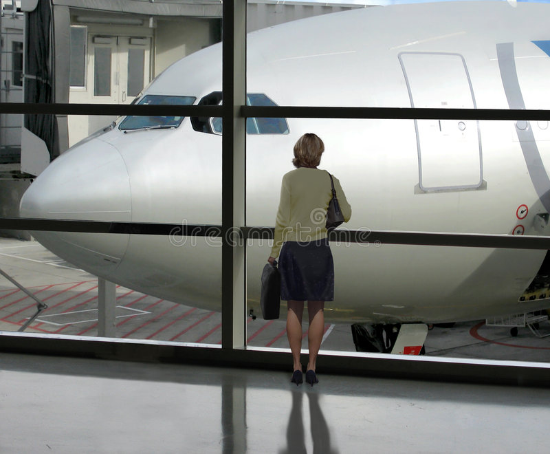 Waiting to board. Businesswoman waits for her flight to board stock image