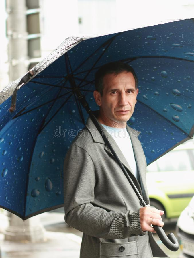 Waiting for the weather to improve. A middle-aged man with a sad face in inclement weather under an umbrella awaits a sunny mood royalty free stock image