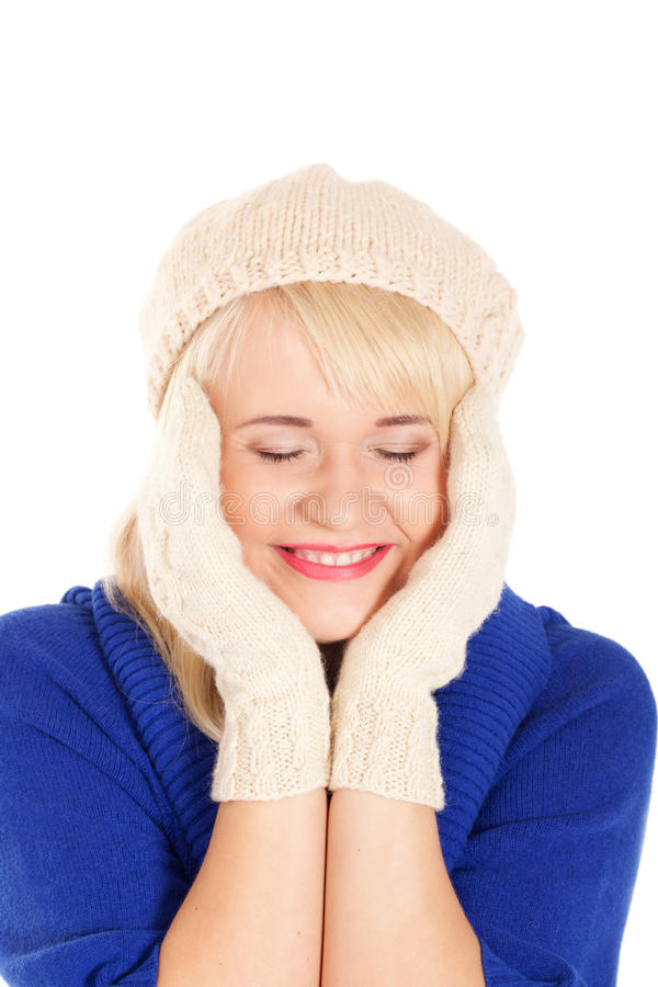 Waiting for the winter. Portrait of beautiful woman with eyes closed in blue sweater and white mitten and beret on isolated white background royalty free stock photography