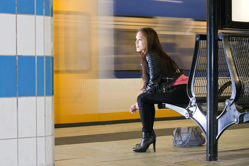 Waiting woman at train station royalty free stock photography