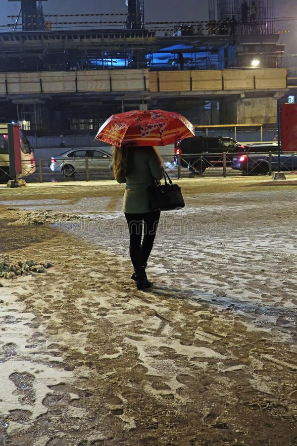Waiting young woman with umbrella in the evening under falling snow. Waiting young woman with umbrella on the street in the evening under falling snow royalty free stock photo