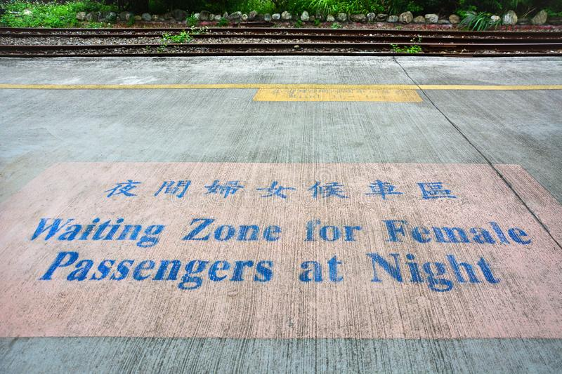 Waiting zone for female passengers at night text sign painted on cement floor with pink background in train platform. Or railway station, Taipei, Taiwan stock photography
