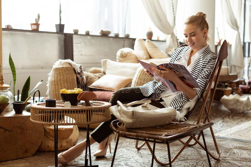 Interested young woman waiting in SPA salon and reading. Waiting zone. Interested young women waiting in SPA salon and reading beauty magazines stock image
