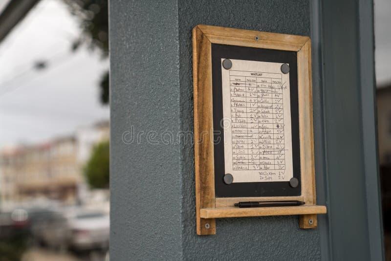 Waitlist füllte mit Namen an hängender Außenseite des populären Restaurantstandorts stockfotografie