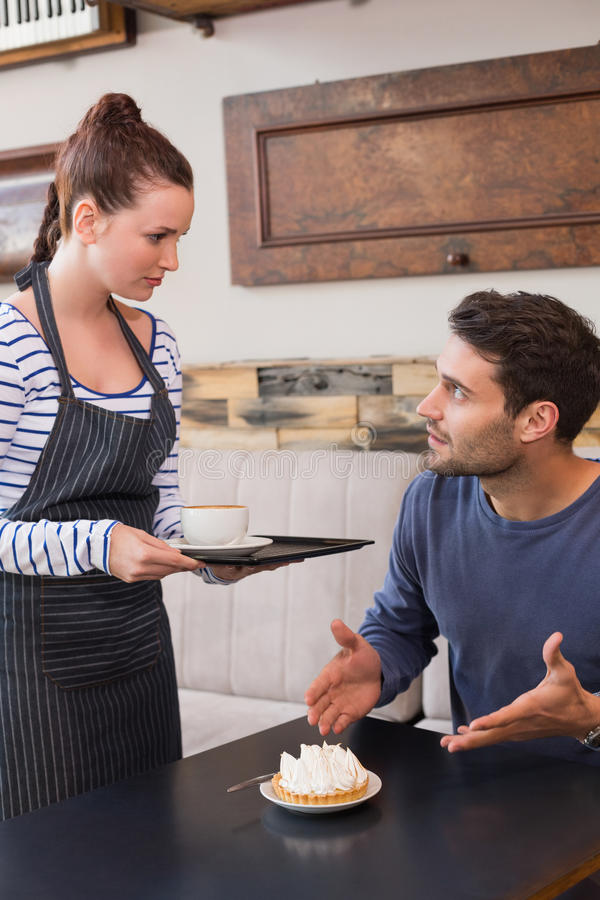 Waitress bringing man coffee and tart. Waitress bringing men coffee and tart at the cafe stock images