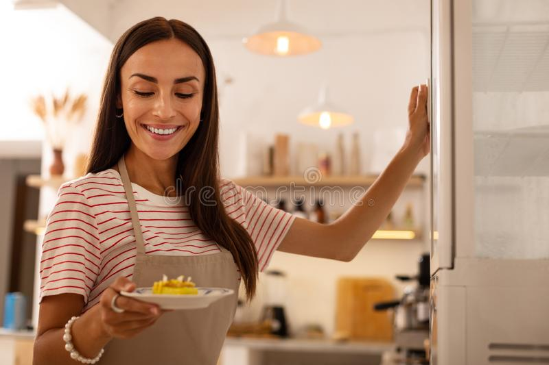 Waitress of cafeteria holding plate with little cake stock photography