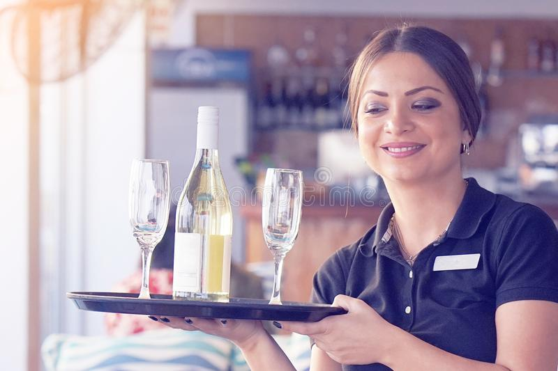 The waitress is carrying a bottle of wine royalty free stock photos