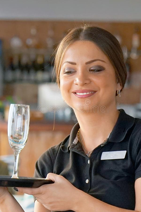 The waitress is carrying a wine glasses royalty free stock image