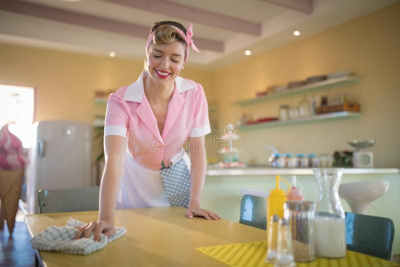 Waitress cleaning the table in restaurant. Young waitress cleaning the table in restaurant stock photos