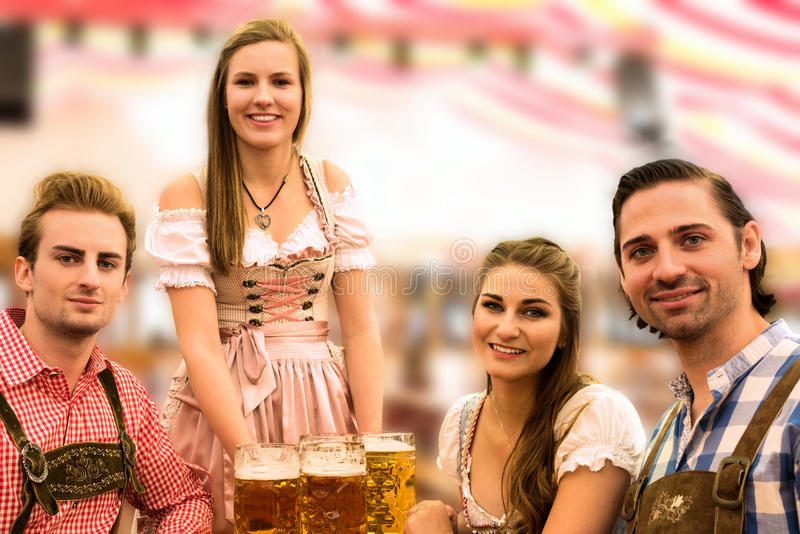 Waitress delivers beers in tent with happy visitors in a beer tent at Munich Oktoberfest stock photos