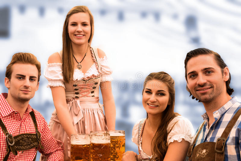 Waitress delivers beers in tent with happy visitors in a beer tent at Munich Oktoberfest. Against blurred blue background royalty free stock photography