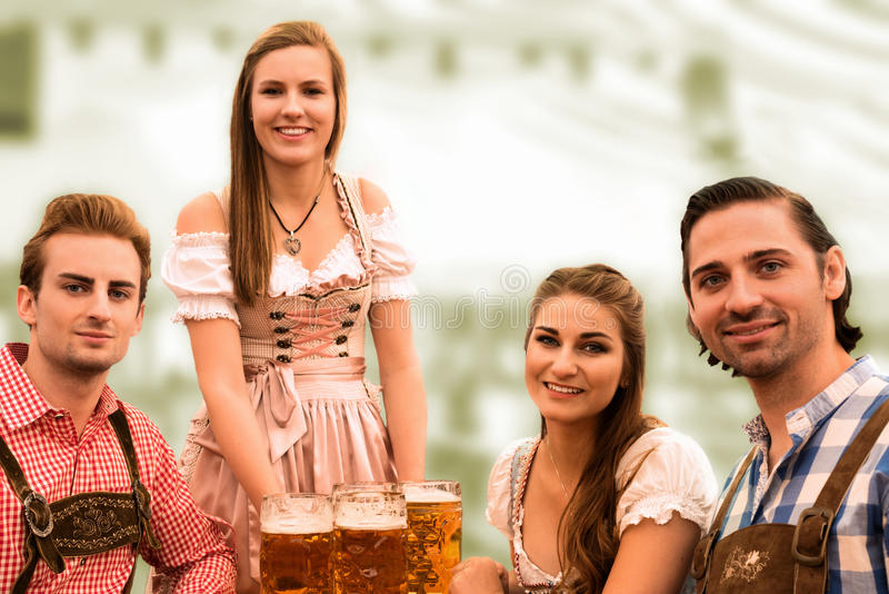 Waitress delivers beers in tent with happy visitors in a beer tent at Munich Oktoberfest. Against blurred greenish background stock photo
